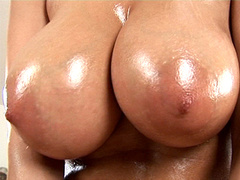 Busty porn bombshell oils her body and rubs pussy